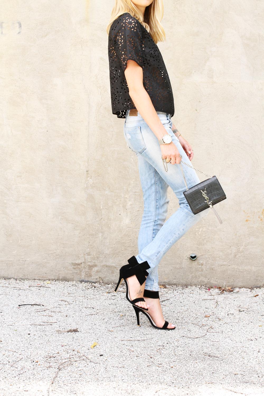 black laser cut top-ripped denim jeans-black bow heels-silver aviator sunglasses-ysl crossbody