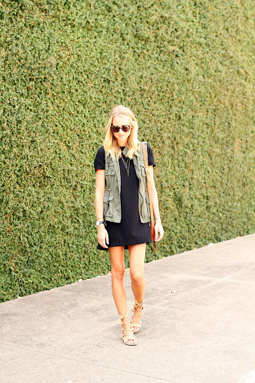 fashion-jackson-short-sleeve-black-dress-olive-utility-vest-gold-layered-necklace-karen-walker-number-one-sunglasses-schutz-gladiator-lace-up-sandals