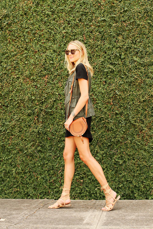 fashion-jackson-short-sleeve-black-dress-olive-utility-vest-karen-walker-number-one-sunglasses-chloe-marcie-small-crossbody-schutz-gladiator-lace-up-sandals