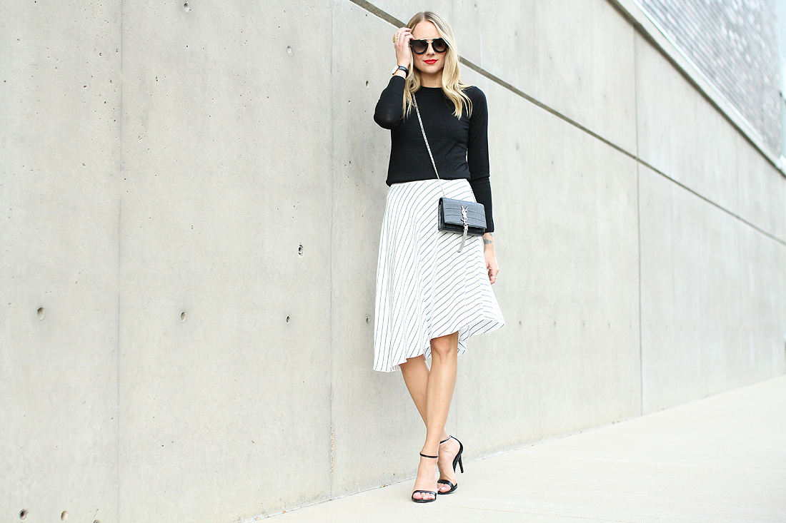 fashion-jackson-club-monaco-white-asymmetrical-skirt-black-sweater-prada-sunglasses-black-ankle-strap-heels-saint-laurent-black-tassel-crossboy