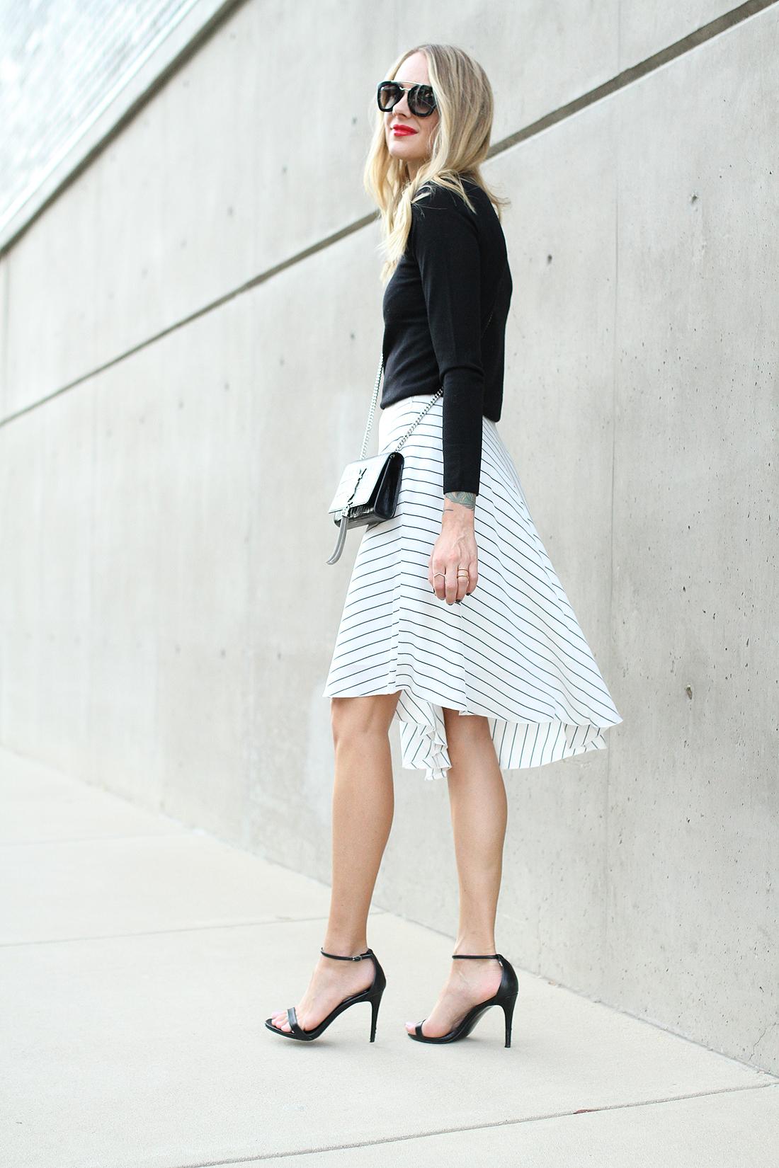 fashion-jackson-club-monaco-white-asymmetrical-skirt-black-sweater-prada-sunglasses-black-ankle-strap-heels