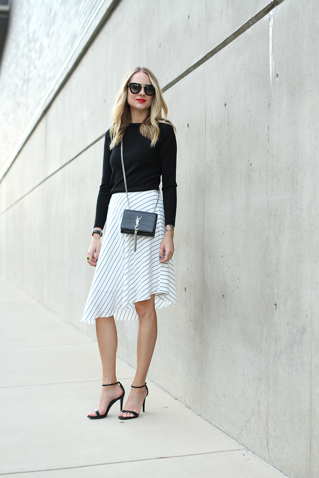 fashion-jackson-club-monaco-white-asymmetrical-skirt-black-sweater-saint-laurent-crossbody-prada-sunglasses