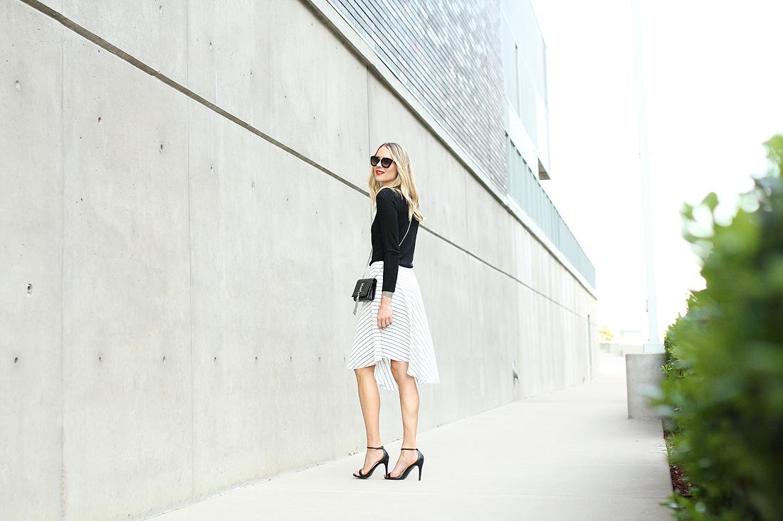fashion-jackson-club-monaco-white-asymmetrical-skirt-black-sweater-saint-laurent-tassel-crossbody-prada-sunglasses-black-ankle-strap-heels