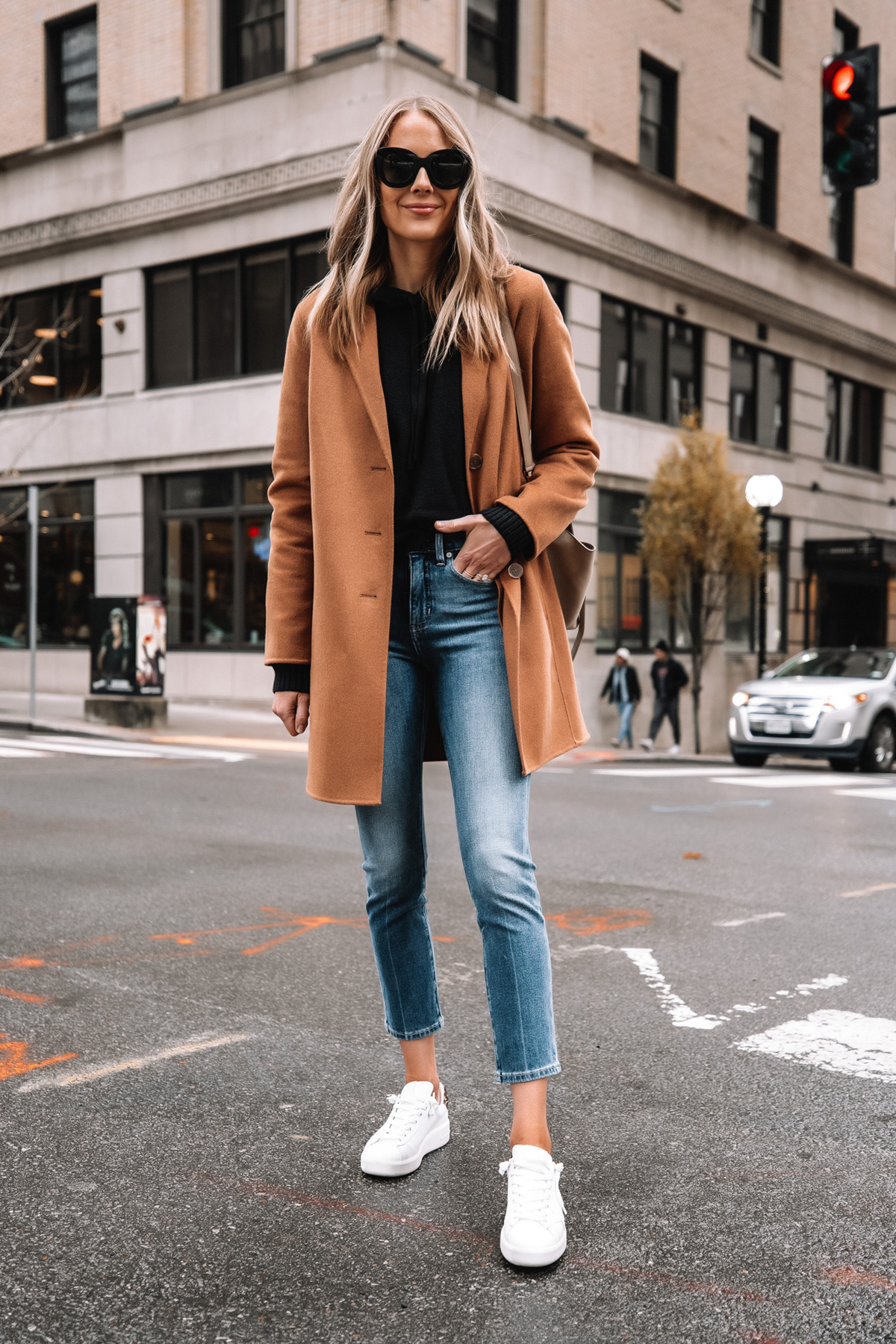 Fashion Jackson Wearing Banana Republic Camel Coat Black Hoodie Sweater Denim Ankle Jeans White Sneakers Street Style