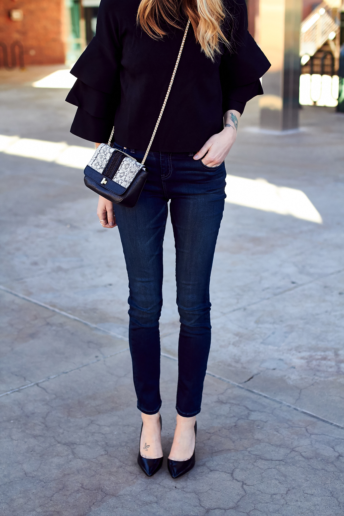 New Year's Eve Outfit, Embellished Handbag, Black Pumps, Black Ruffle Sleeve Top, Denim Skinny Jeans