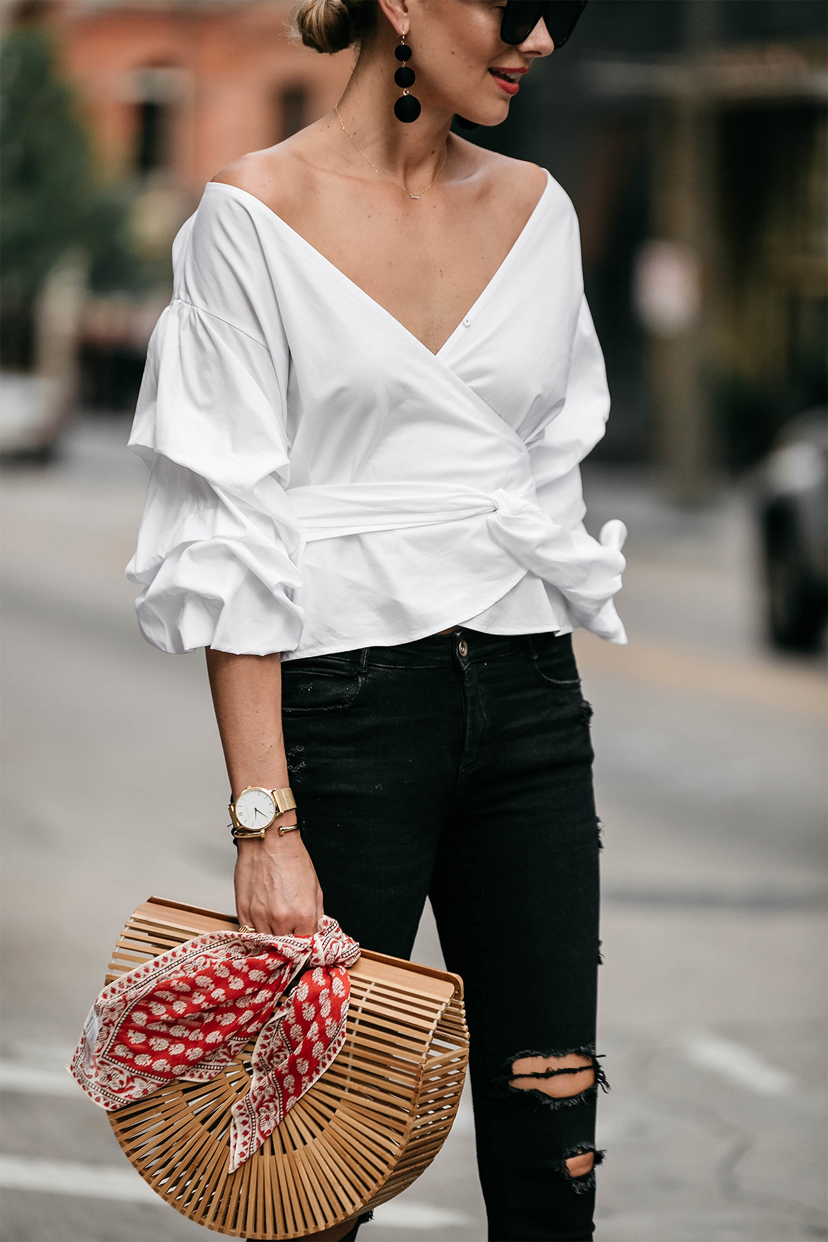 Woman Wearing Club Monaco Ruffle Sleeve Wrap Top Cult Gaia Ark Bag Red Bandana Black Ripped Skinny Jeans Street Style Outfit