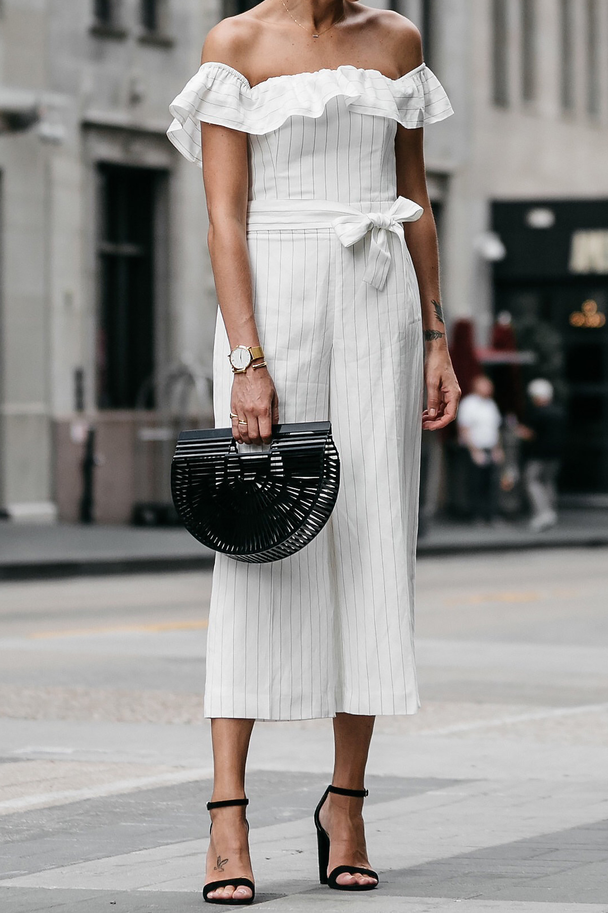 Woman wearing Club Monaco off-the-shoulder ruffle white jumpsuit Black Ankle Strap Heeled Sandals Cult Gaia Black Acrylic Ark Clutch