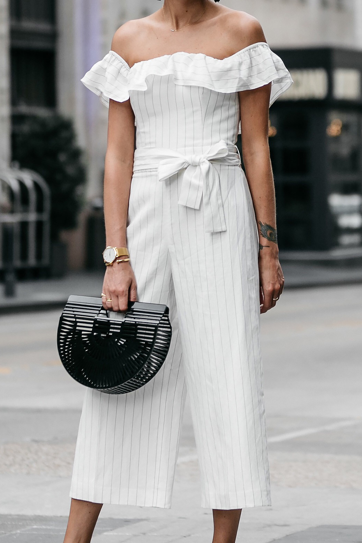 Woman wearing Club Monaco off-the-shoulder ruffle white jumpsuit Cult Gaia Black Acrylic Ark Clutch