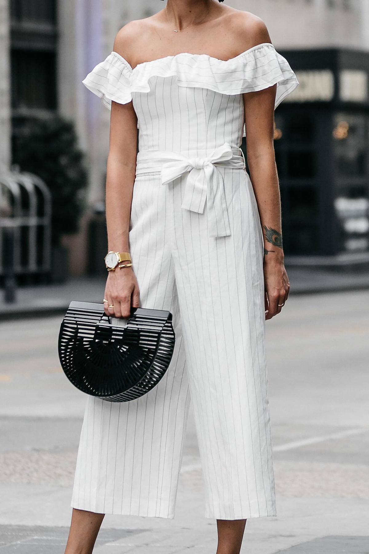 Woman wearing Club Monaco off-the-shoulder ruffle white jumpsuit Cult Gaia Black Acrylic Ark Clutch