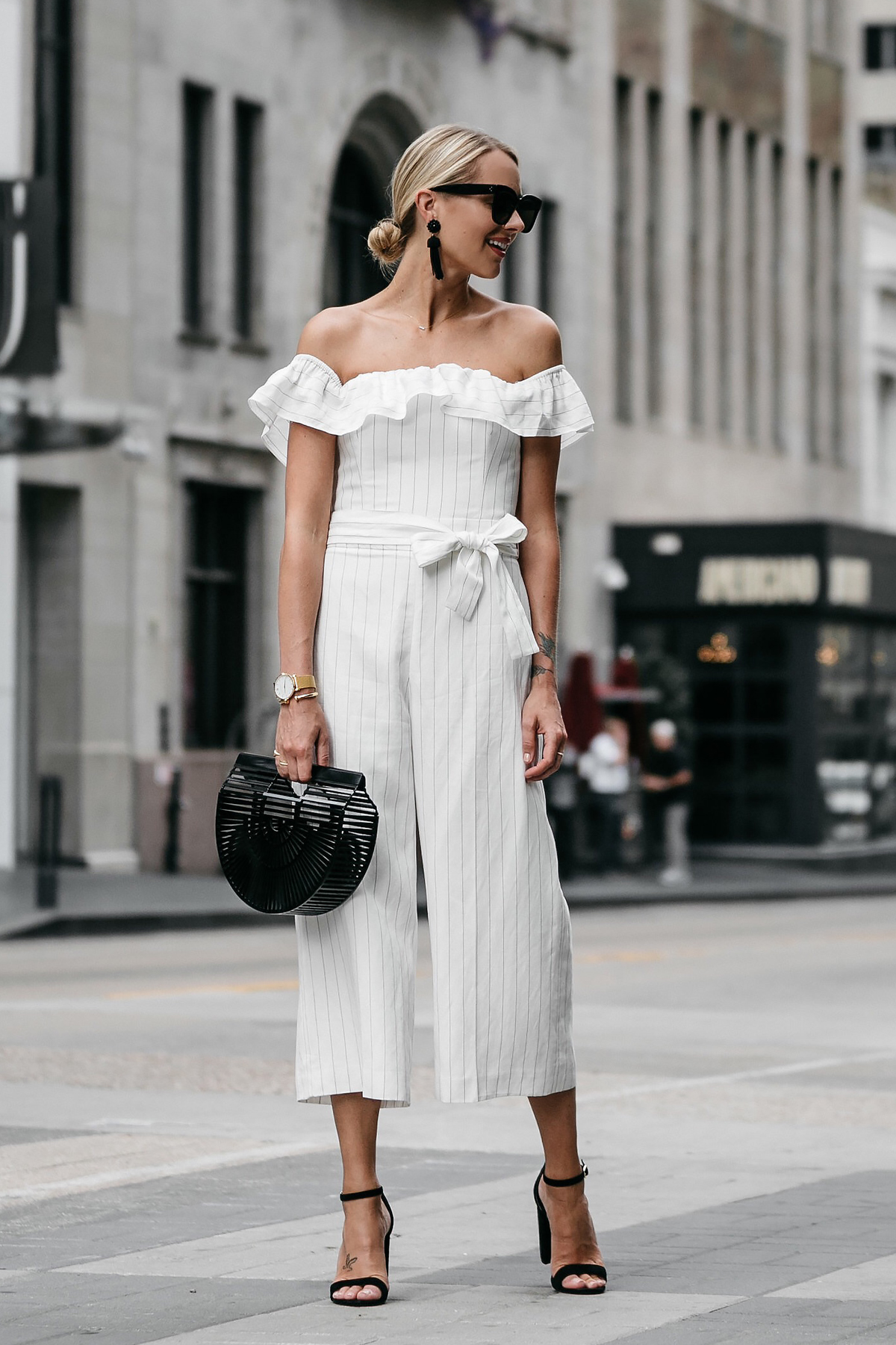 Blonde woman wearing Club Monaco off-the-shoulder ruffle white jumpsuit Cult Gaia Black Acrylic Ark Clutch Black Ankle Strap Heeled Sandals Black Tassel Earrings