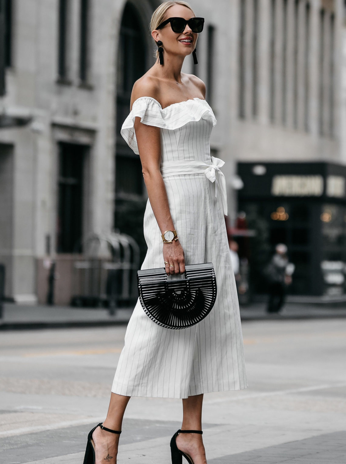 Blonde woman wearing Club Monaco white off-the-shoulder ruffle jumpsuit Cult Gaia Black Acrylic Ark Clutch Black Ankle Strap Heeled Sandals Black Tassel Earrings