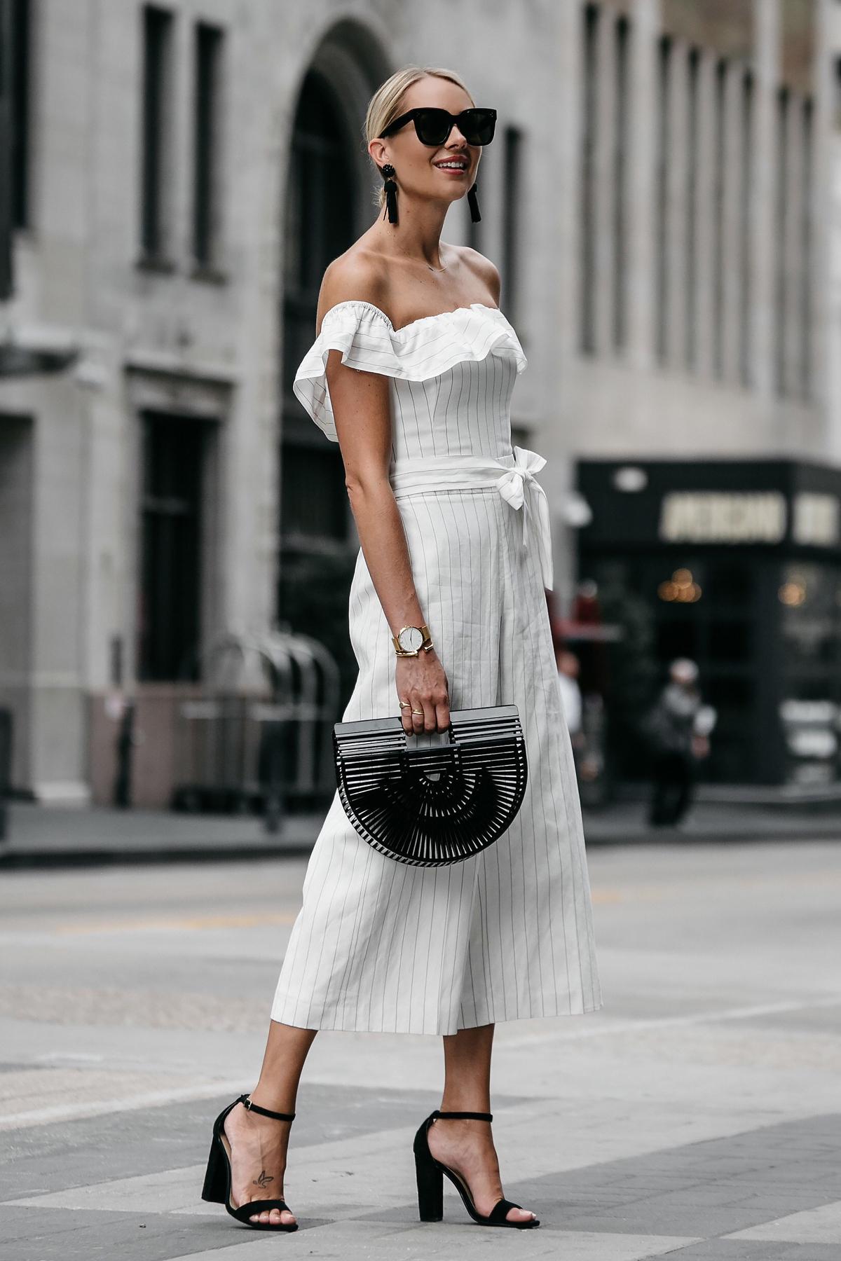 Blonde woman wearing Club Monaco off-the-shoulder ruffle white jumpsuit Cult Gaia Black Acrylic Ark Clutch Black Ankle Strap Heeled Sandals Black Tassel Earrings