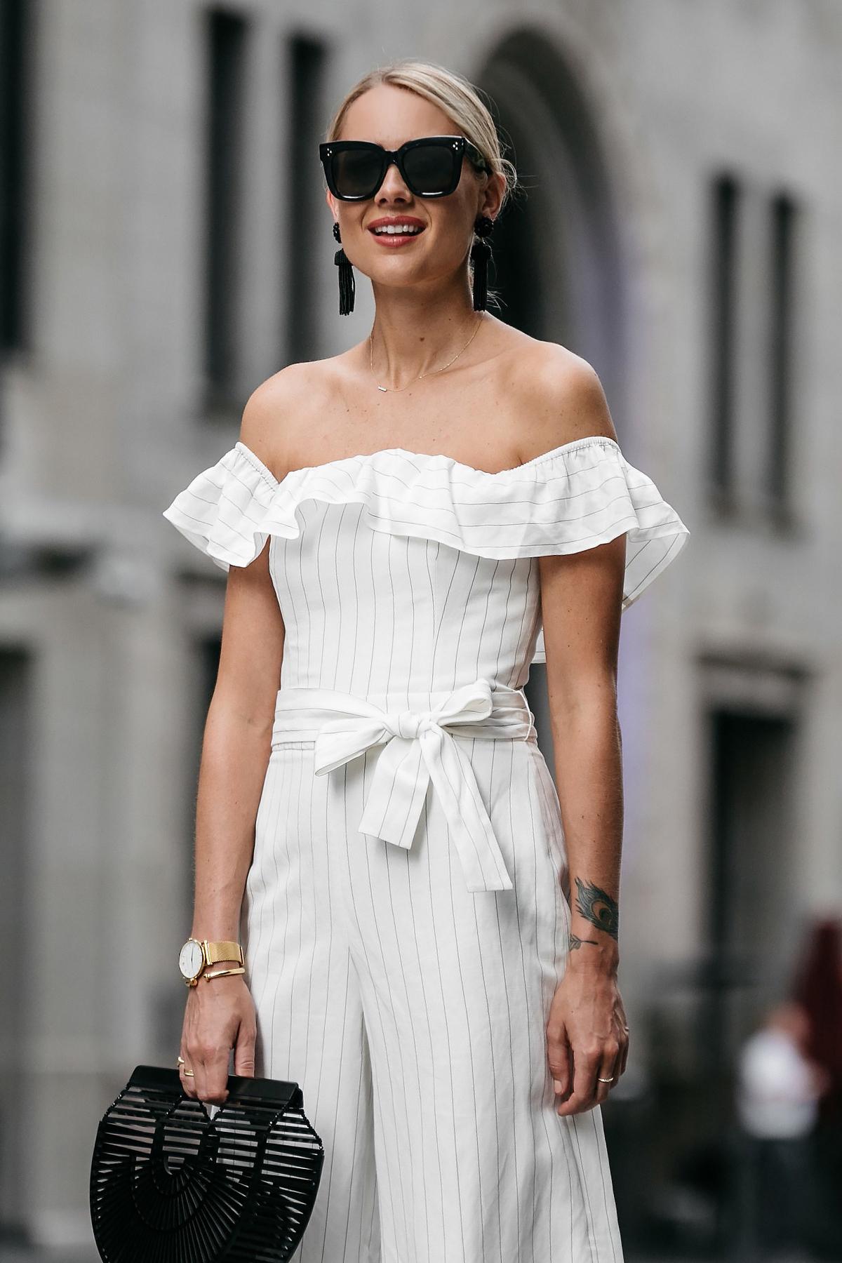Blonde woman wearing Club Monaco off-the-shoulder ruffle white jumpsuit Cult Gaia Black Acrylic Ark Clutch Black Tassel Earrings