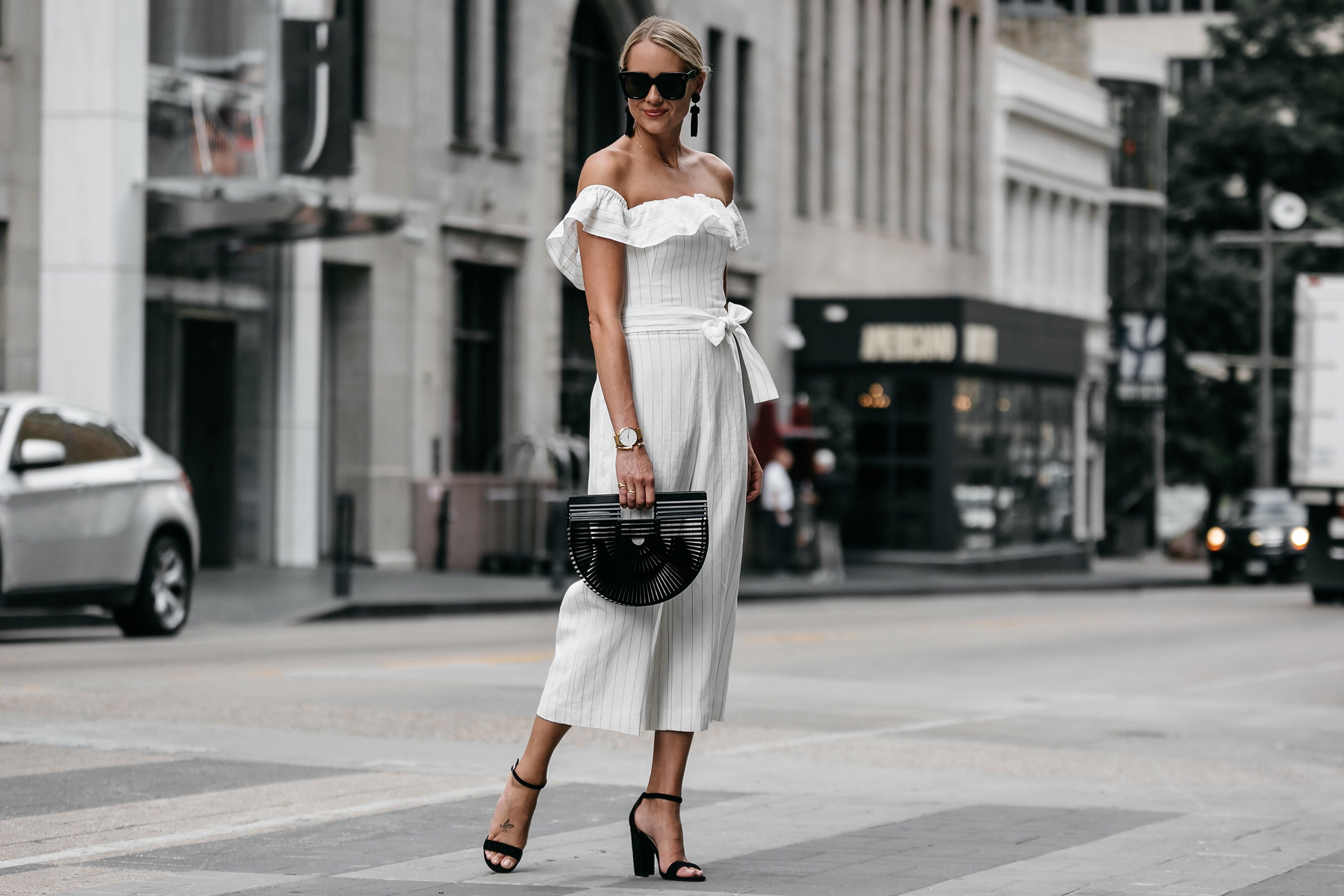 Blonde woman wearing Club Monaco off-the-shoulder ruffle white jumpsuit Cult Gaia Black Acrylic Ark Clutch Black Ankle Strap Heeled Sandals