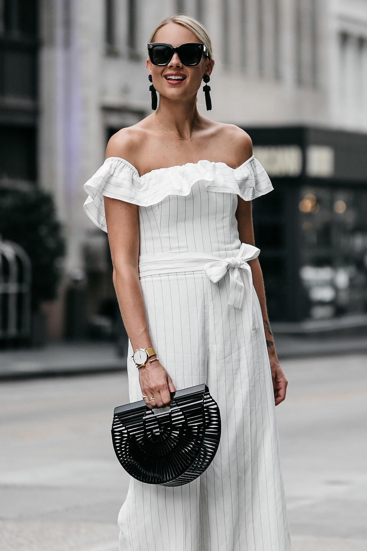 Blonde woman wearing Club Monaco off-the-shoulder ruffle white jumpsuit Cult Gaia Black Acrylic Ark Clutch Black Tassel Earrings