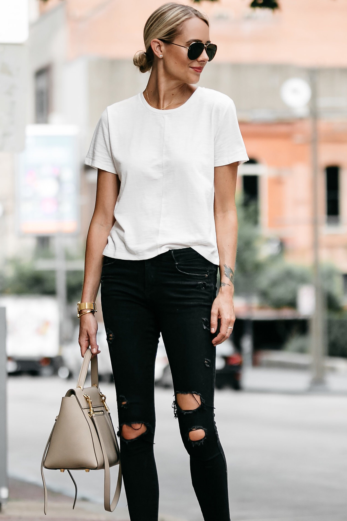 Blonde woman wearing everlane white tshirt zara black ripped skinny jeans outfit celine belt back street style dallas blogger fashion blogger
