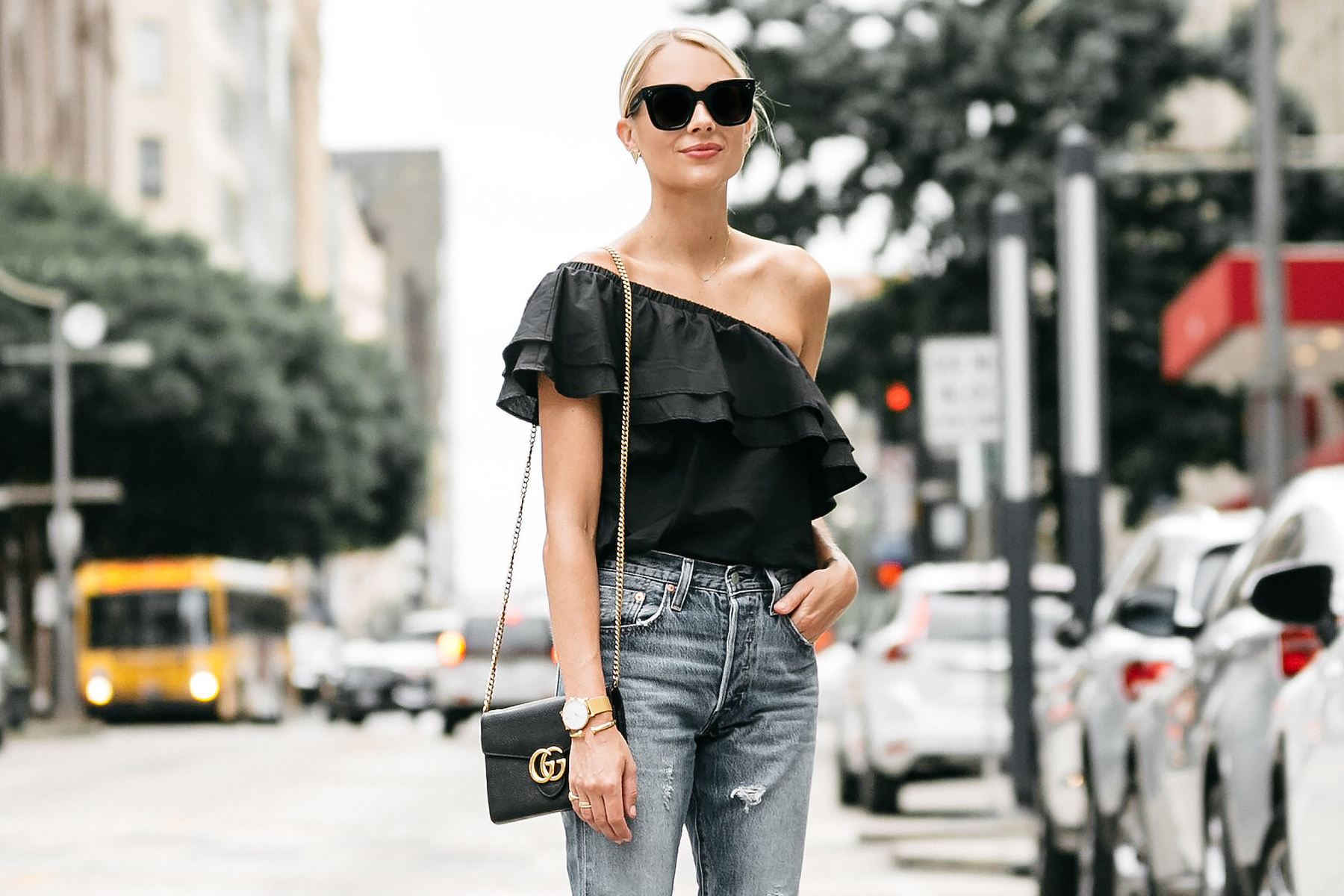 1494308f6a5 Blonde woman wearing nordstrom black one shoulder ruffle top levis  distressed jeans gucci marmont handbag street