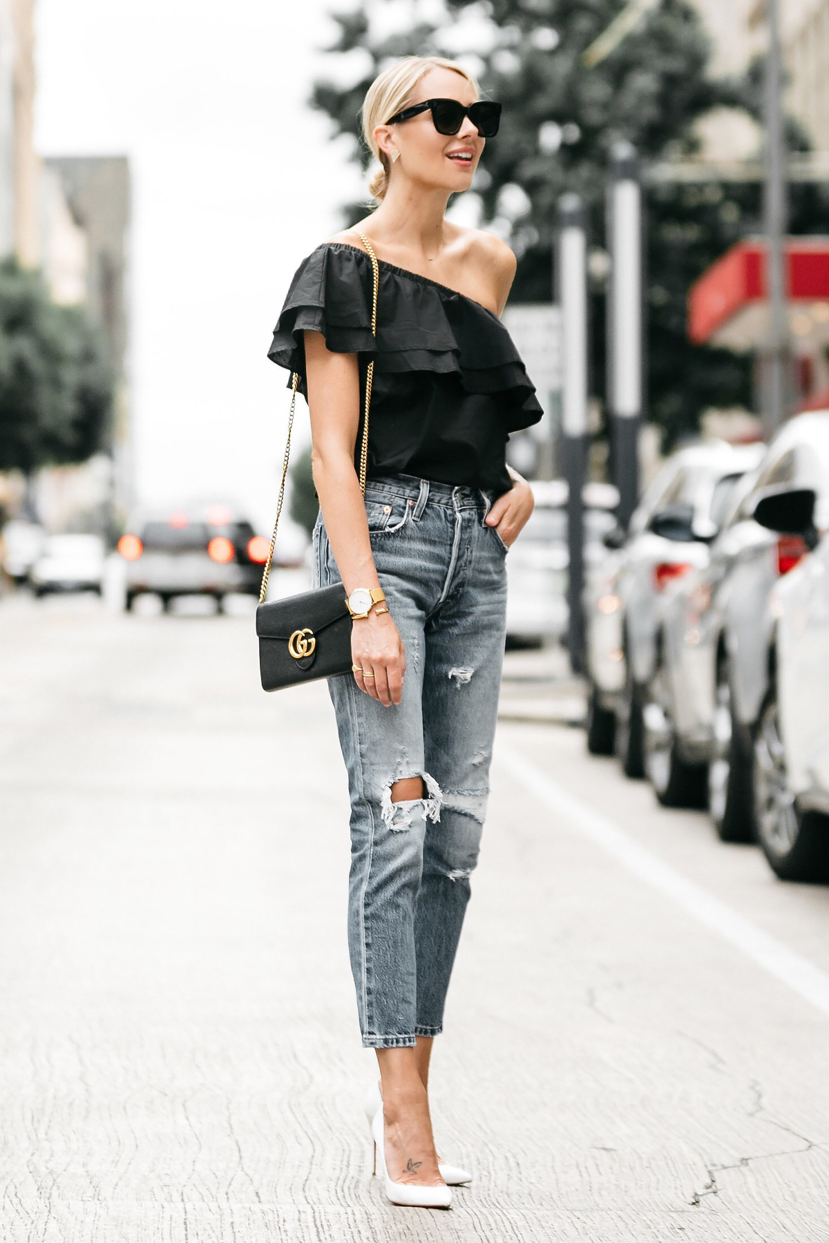 Blonde woman wearing nordstrom black one shoulder ruffle top levis distressed jeans christian louboutin white pumps gucci marmont handbag street style dallas blogger fashion blogger