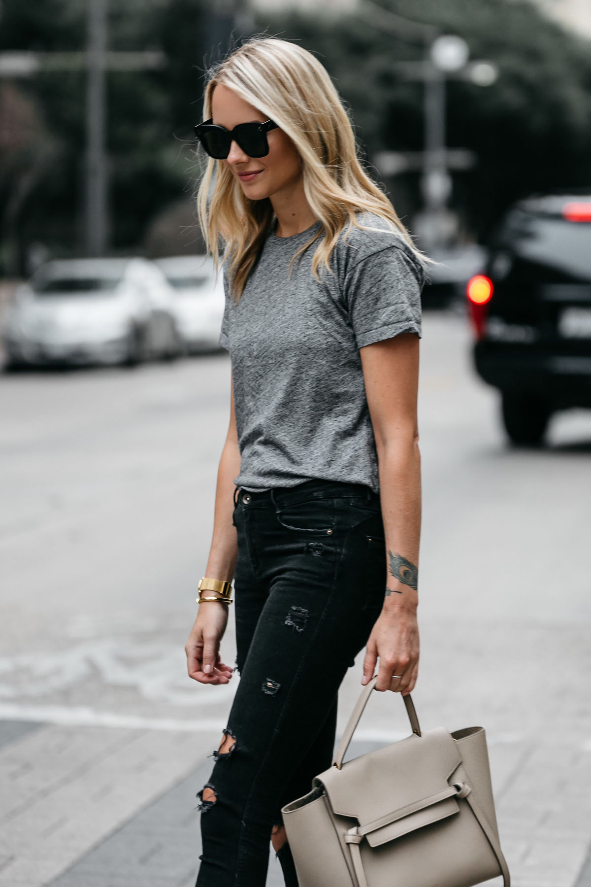 Blonde woman wearing Madewell grey tshirt zara black ripped skinny jeans outfit celine belt bag street style dallas blogger fashion blogger