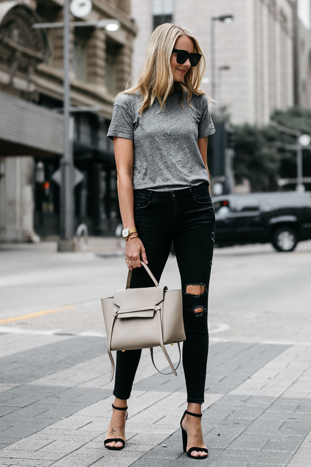 Blonde woman wearing Madewell grey tshirt zara black ripped skinny jeans outfit steve madden black ankle strap heels celine belt bag street style dallas blogger fashion blogger