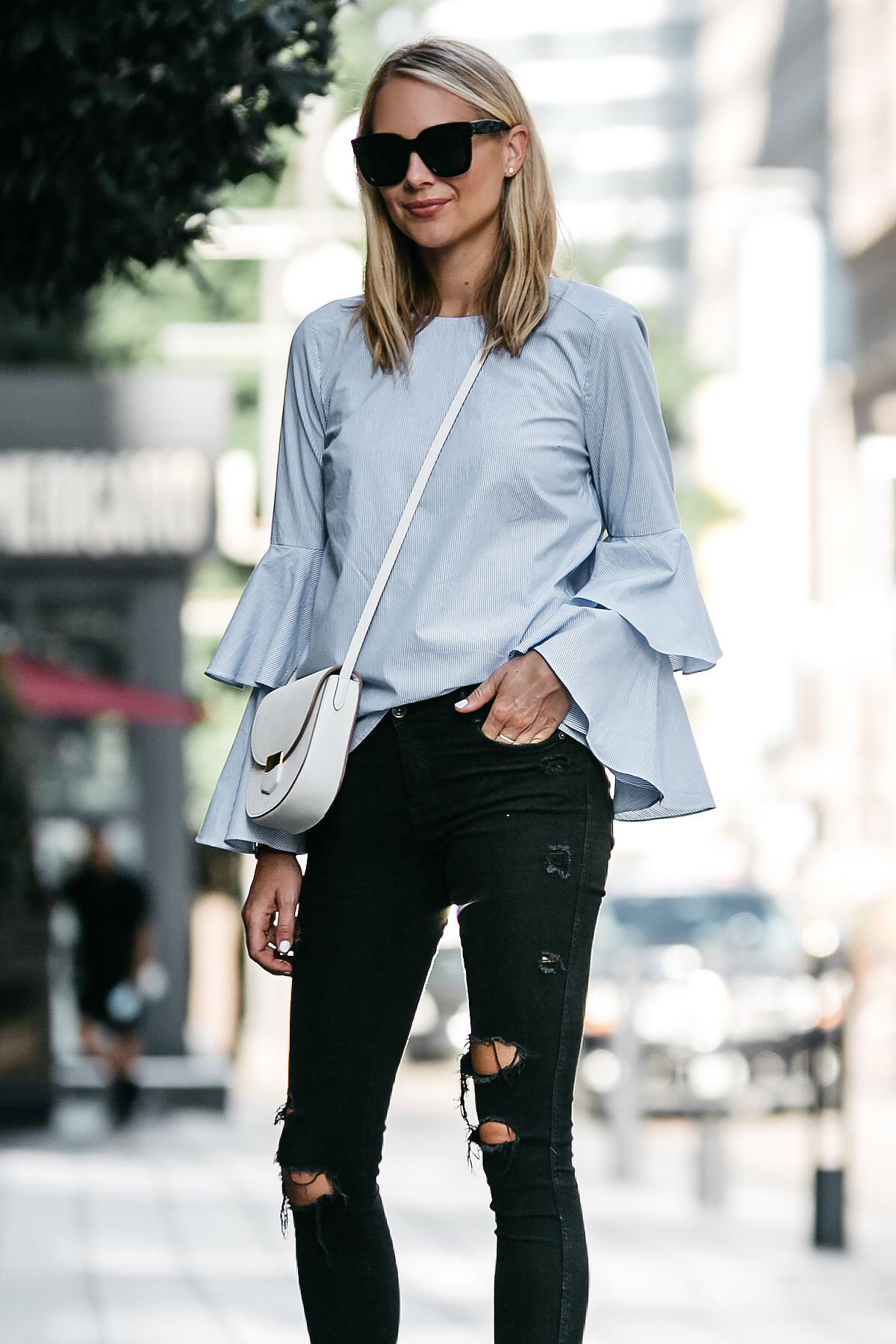 Blonde Woman Wearing Nordstrom Blue Bell Sleeve Top Black Ripped Skinny Jeans Outfit Celine Trotteur White Crossbody Fashion Jackson Dallas Blogger Fashion Blogger Street Style