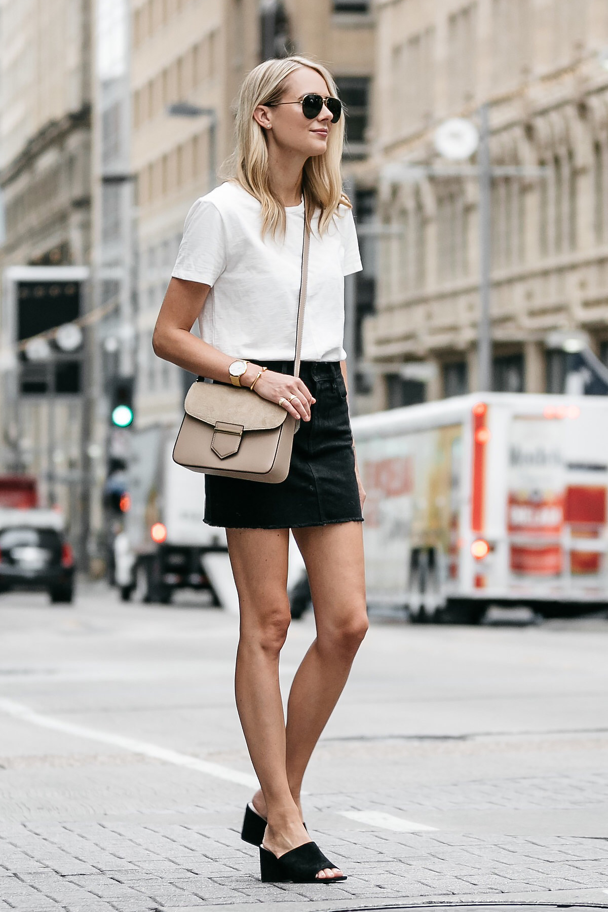 Blonde woman wearing white tshirt frame black denim skirt outfit black mules tan crossbody handbag street style dallas blogger fashion blogger