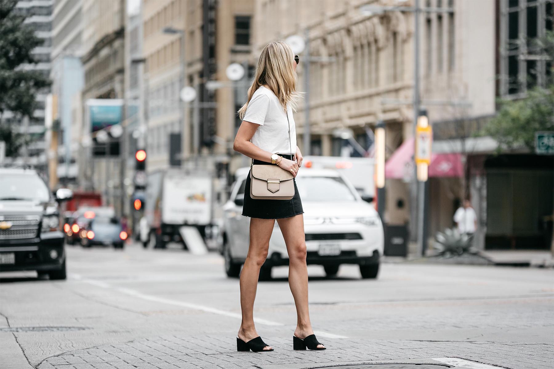 Blonde woman wearing white tshirt frame black denim skirt outfit black mules tan crossbody handbag street style dallas blogger fashion blogger