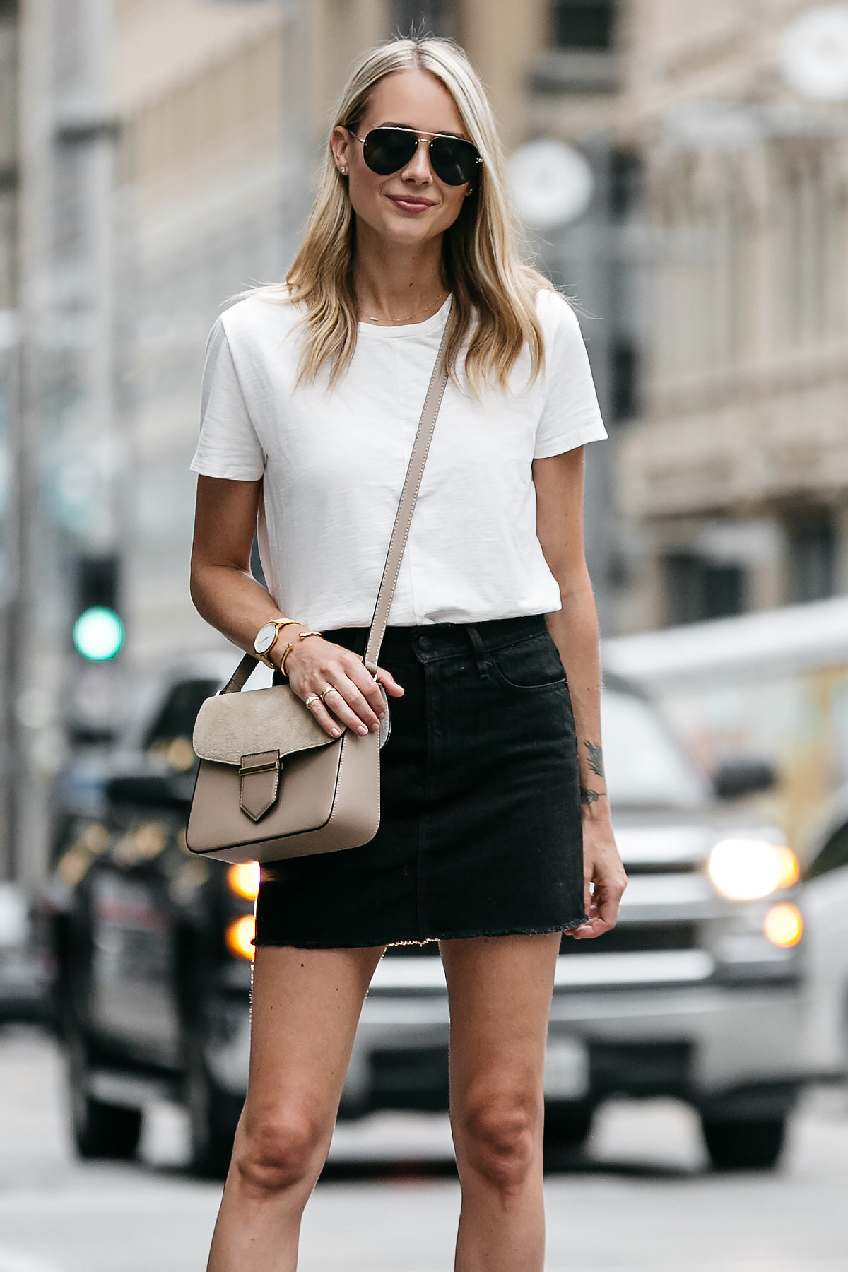 Blonde woman wearing white tshirt frame black denim skirt outfit tan crossbody handbag street style dallas blogger fashion blogger