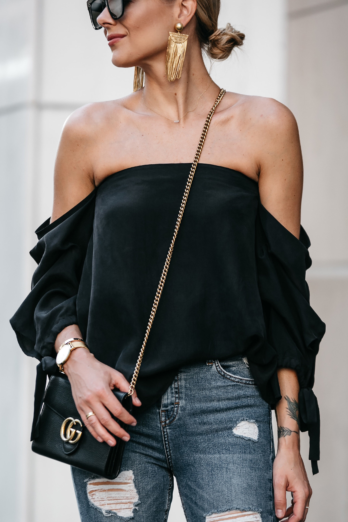 Blonde Woman Wearing Club Monaco Black Off-the-Shoulder Top Large Gold Tassel Earrings Gucci Marmont Handbag