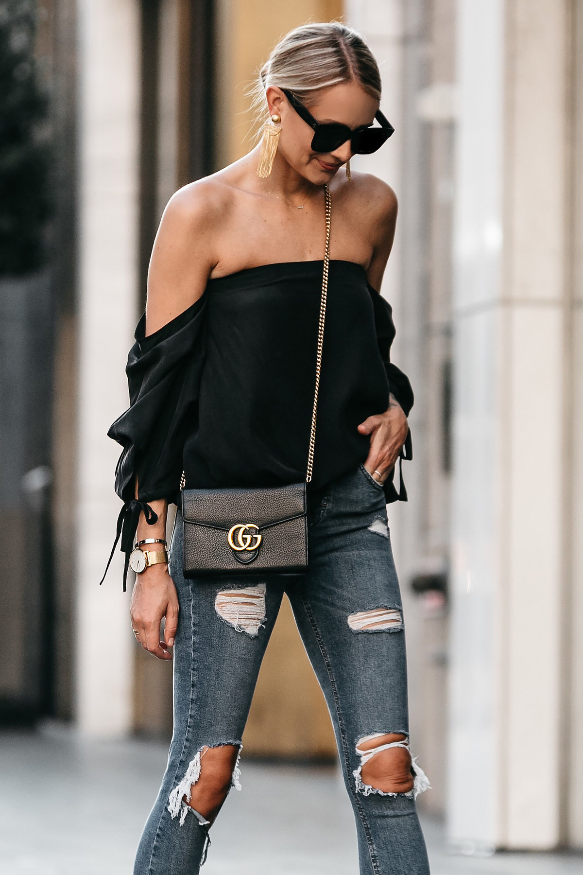 Blonde Woman Wearing Club Monaco Black Off-the-Shoulder Top Gucci Marmont Handbag Denim Ripped Skinny Jeans