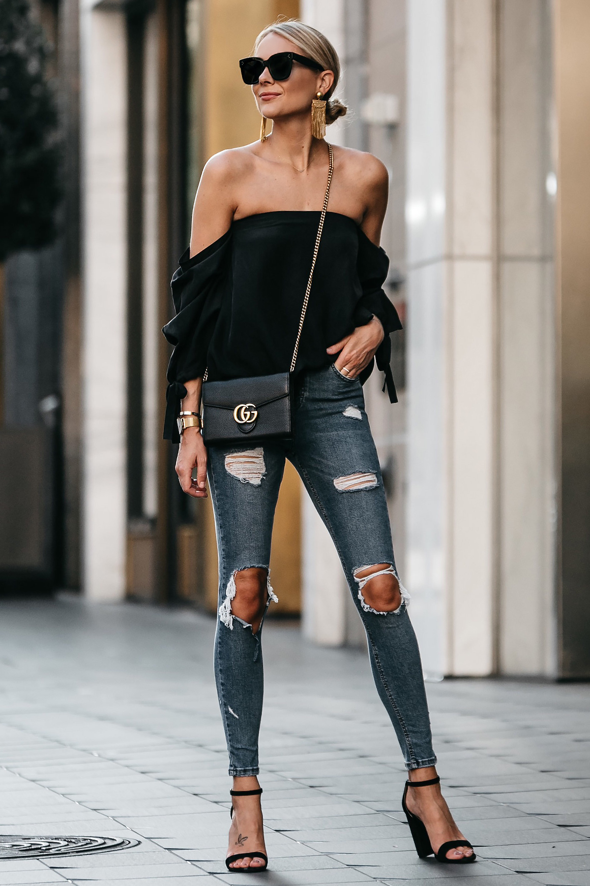 Blonde Woman Wearing Club Monaco Black Off-the-Shoulder Top Denim Ripped Skinny Jeans Outfit Black Ankle Strap Heels Gucci Marmont Handbag