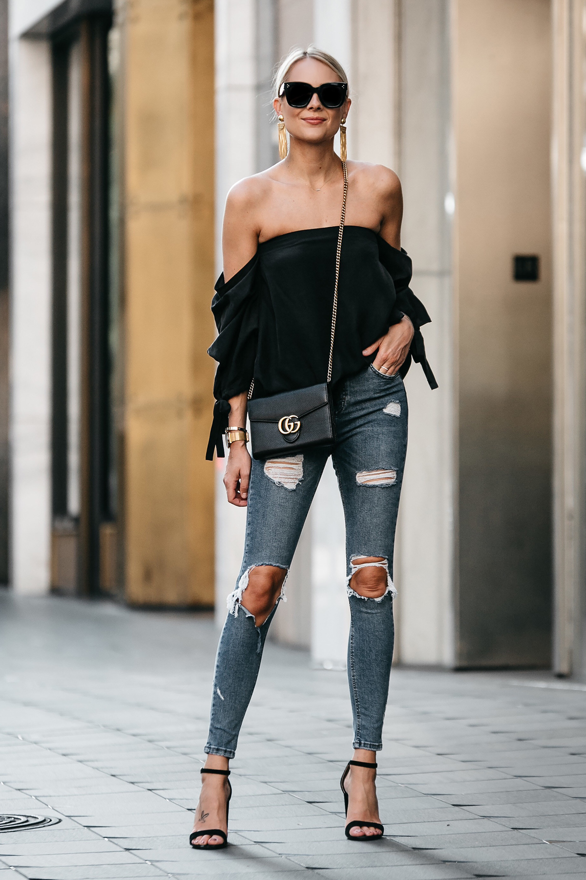 Blonde Woman Wearing Club Monaco Black Off-the-Shoulder Top Denim Ripped Skinny Jeans Outfit Gucci Marmont Handbag Black Ankle Strap Heeled Sandals