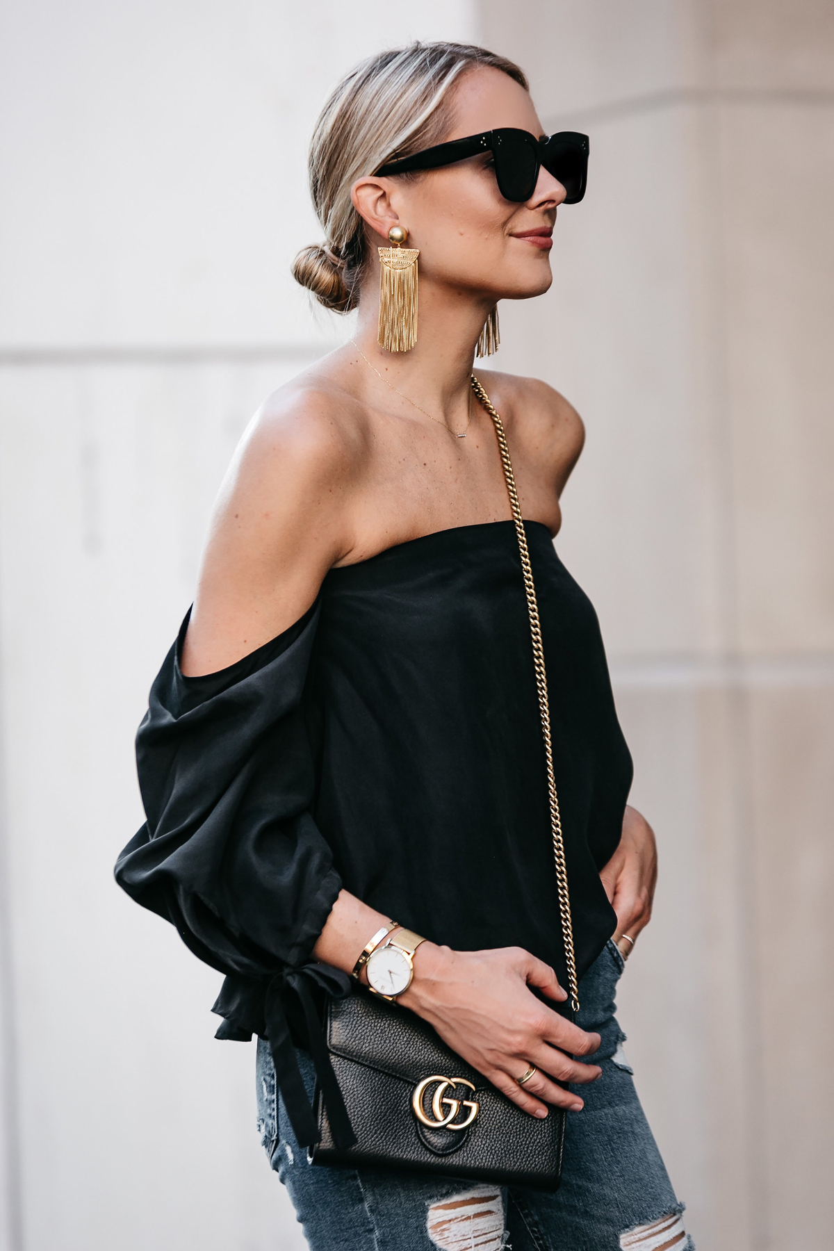 Blonde Woman Wearing Club Monaco Black Off-the-Shoulder Top Gucci Marmont Handbag Large Gold Tassel Earrings