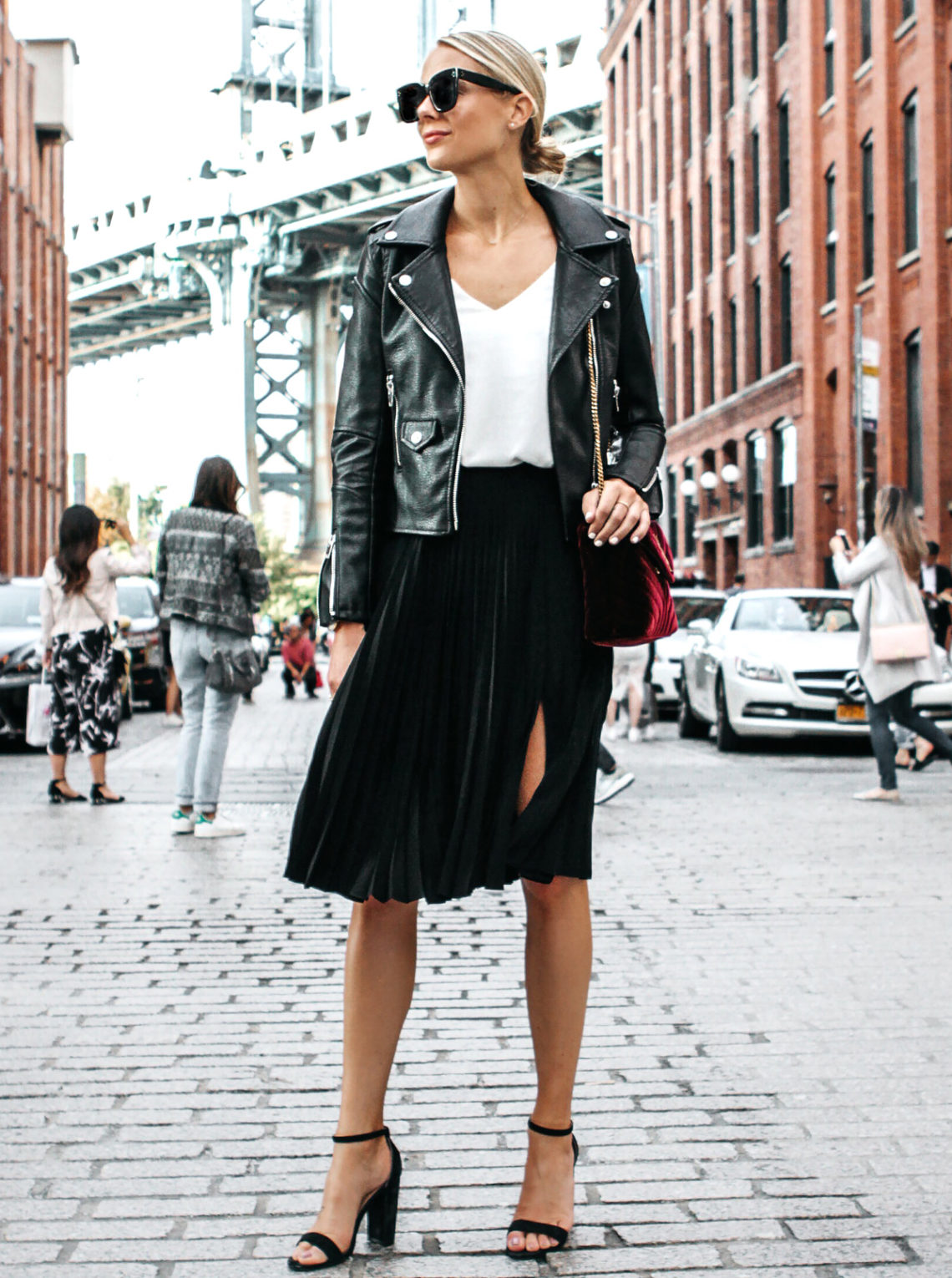Blonde Woman Wearing Black Leather Jacket Black Pleated Midi Skirt Saint Laurent Burgundy Velvet Bag Black Ankle Strap Heeled Sandals Fashion Jackson Dallas Blogger Fashion Blogger Street Style NYFW Dumbo Bridge