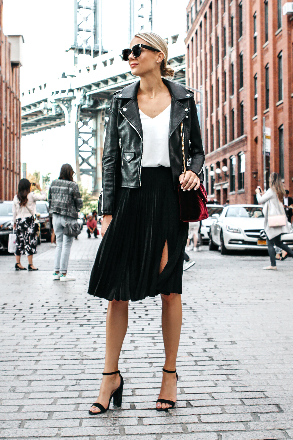c23378c52750 Blonde Woman Wearing Black Leather Jacket Black Pleated Midi Skirt Saint  Laurent Burgundy Velvet Bag Black