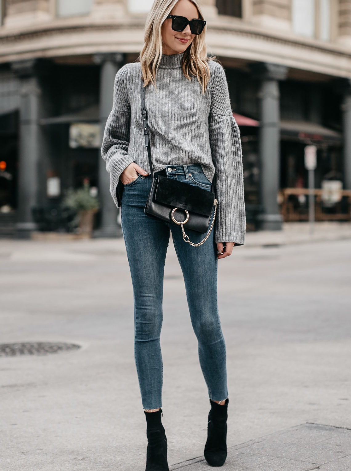 Blonde Woman Wearing Grey Bell Sleeve Sweater Denim Skinny Jeans Chloe Faye Black Handbag Black Booties Fashion Jackson Dallas Blogger Fashion Blogger Street Style