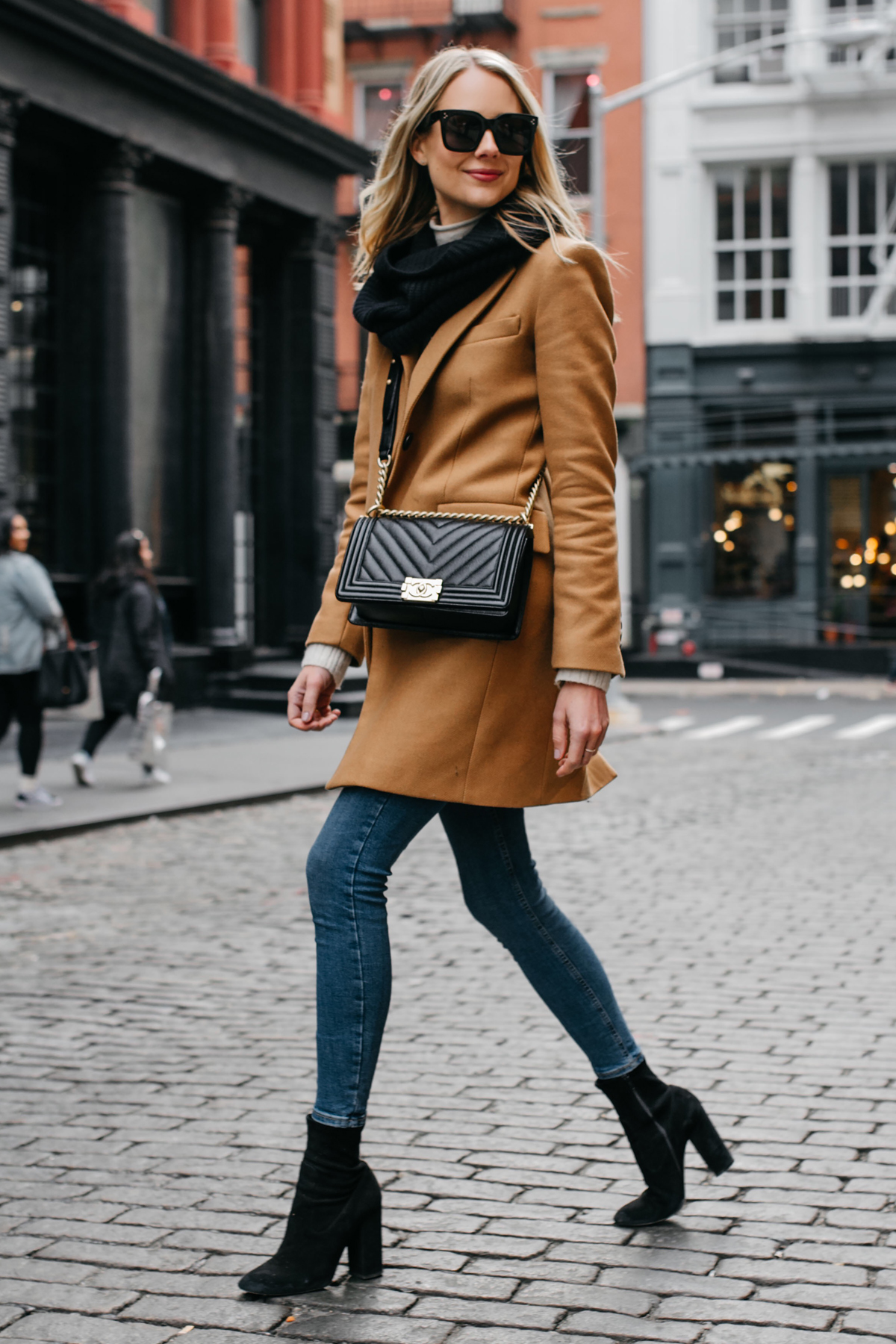Blonde Woman Wearing Camel Coat Black Scarf Denim Skinny Jeans Black Booties Chanel Black Boy Bag Fashion Jackson Dallas Blogger Fashion Blogger NYC Street Style