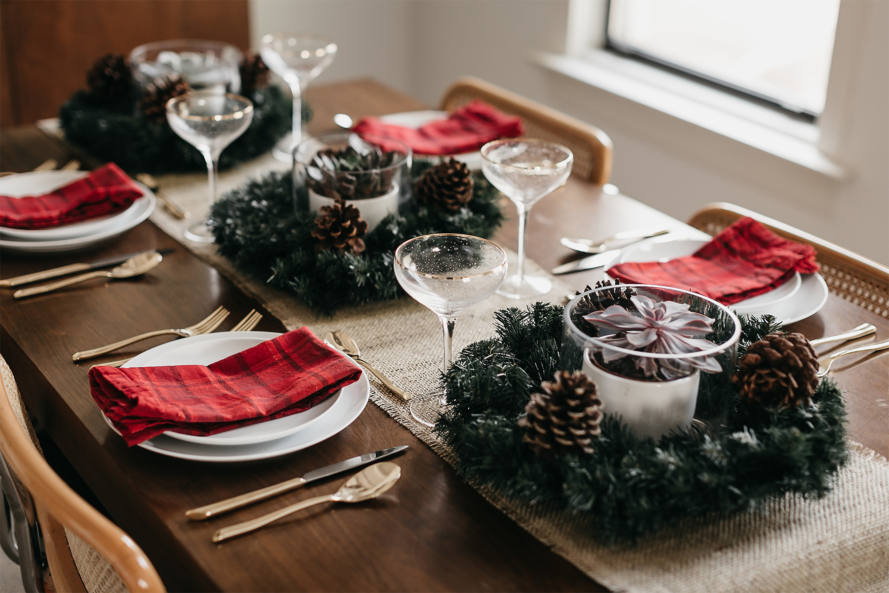 Fashion Jackson Christmas Tablescape Red Plaid Napkins White Dinnerware Gold Flatware Gold Champagne Flutes Wreath Pine Cone Centerpiece 2
