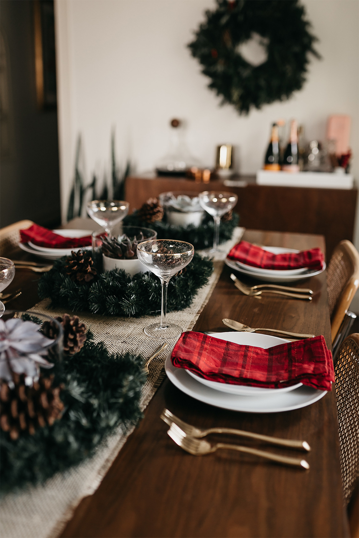 Fashion Jackson Christmas Tablescape Red Plaid Napkins White Dinnerware Gold Flatware Gold Champagne Flutes Wreath Pine Cone Centerpiece 4