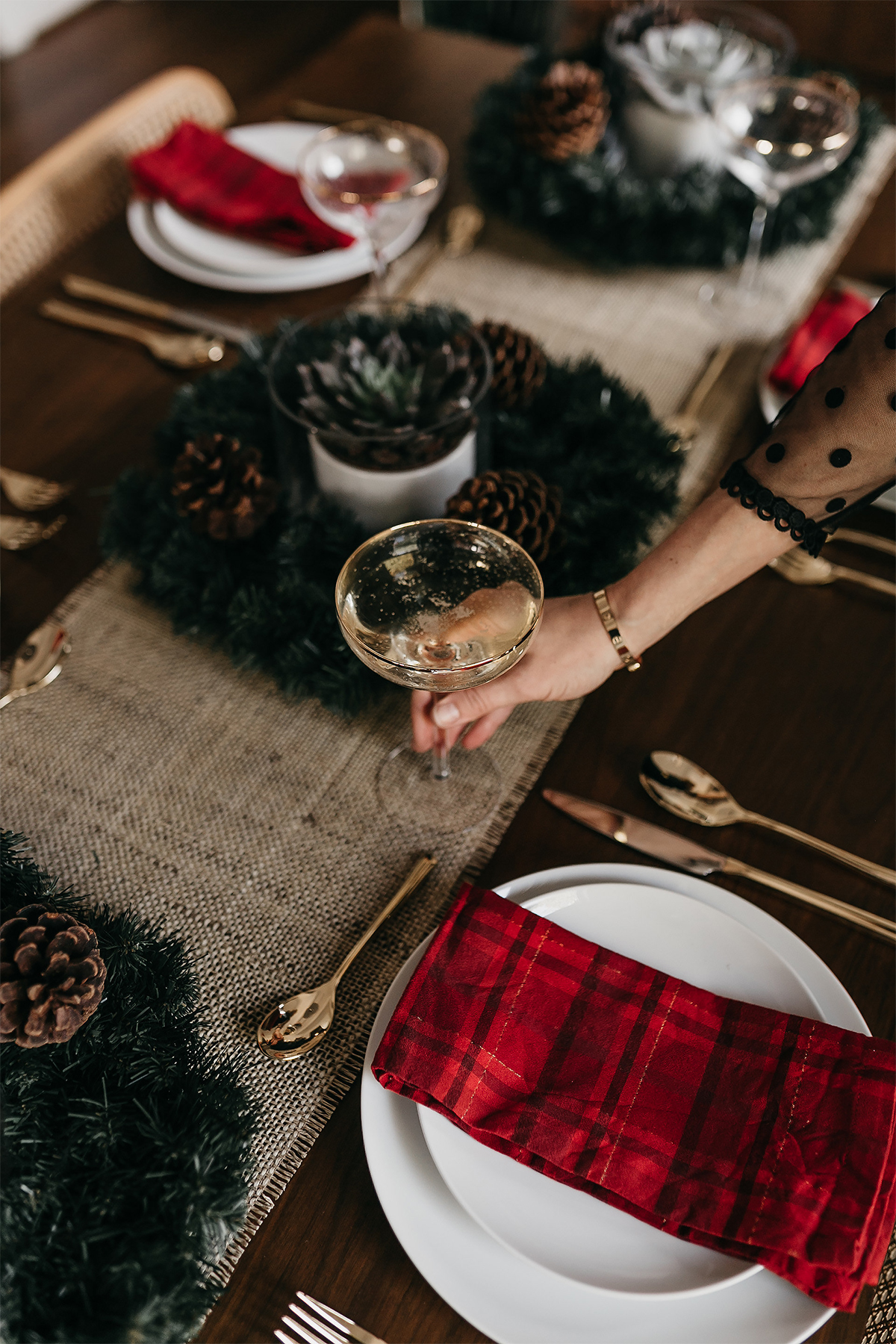 Fashion Jackson Christmas Tablescape Red Plaid Napkins White Dinnerware Gold Flatware Gold Champagne Flutes Wreath Pine Cone Centerpiece 5
