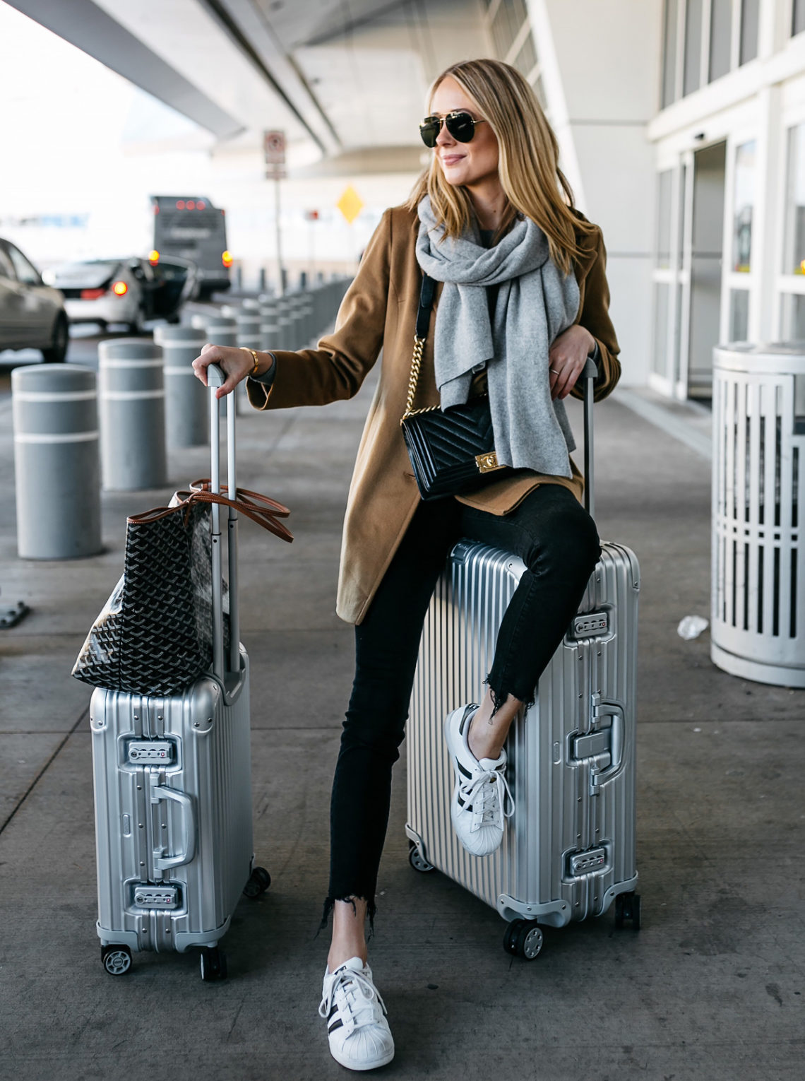 Blonde Woman Wearing Camel Coat Black Ripped Skinny Jeans Grey Scarf Chanel Black Boy Bag adidas Superstar Sneakers Rimowa Luggage Goyard Tote Fashion Jackson Dallas Blogger Fashion Blogger Street Style Airport Style