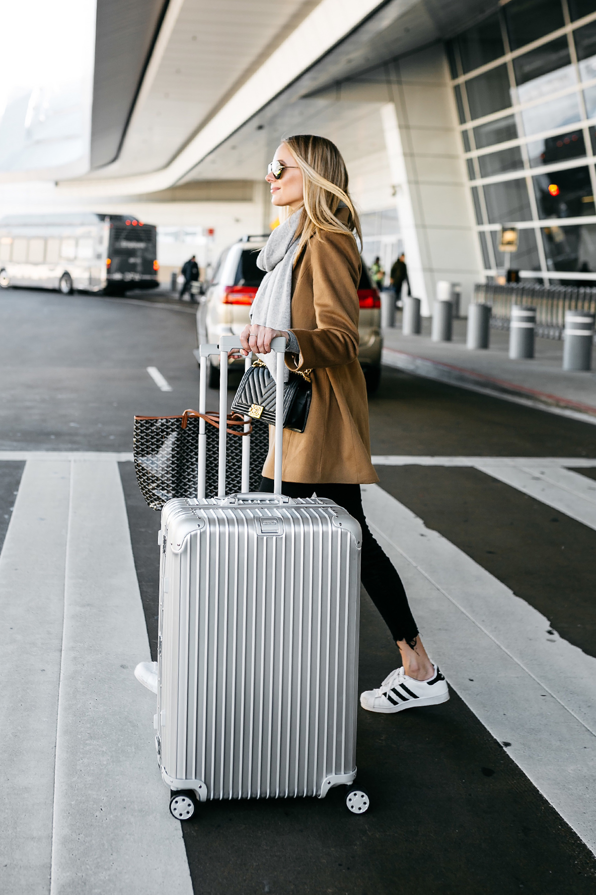 Blonde Woman Wearing Camel Coat Black Ripped Skinny Jeans Grey Scarf Chanel Black Boy Bag adidas Superstar Sneakers Rimowa Luggage Fashion Jackson Dallas Blogger Fashion Blogger Street Style Airport Style
