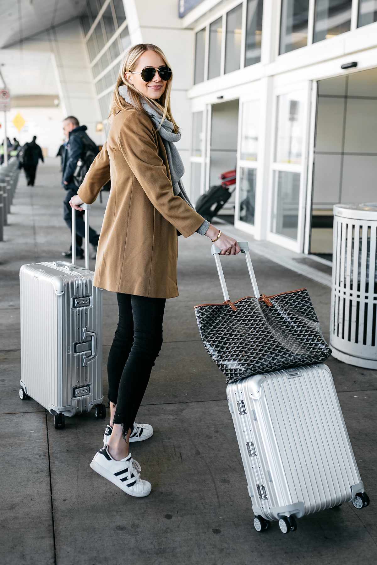 Blonde Woman Wearing Camel Coat Black Ripped Skinny Jeans Grey Scarf adidas Superstar Sneakers Rimowa Luggage Goyard Tote Fashion Jackson Dallas Blogger Fashion Blogger Street Style Airport Style