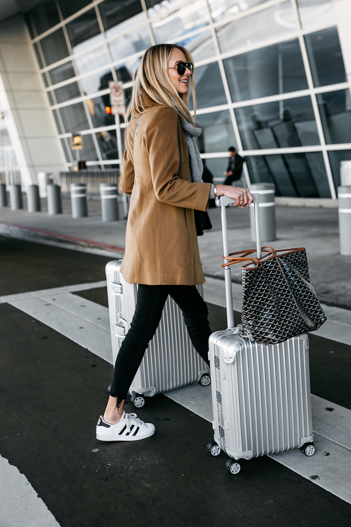 Blonde Woman Wearing Camel Coat Black Ripped Skinny Jeans adidas Superstar Sneakers Rimowa Luggage Fashion Jackson Dallas Blogger Fashion Blogger Street Style Airport Style