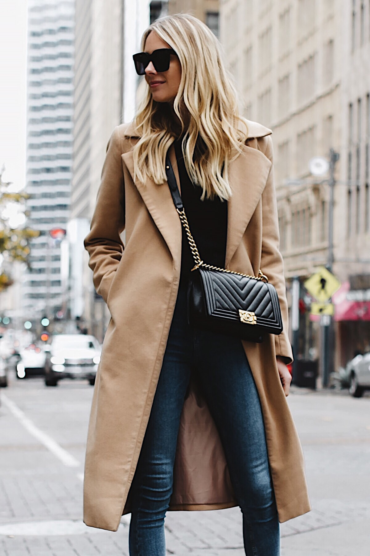 blonde woman wearing long camel coat black sweater topshop denim skinny jeans chanel black boy bag fashion jackson dallas blogger fashion blogger street style