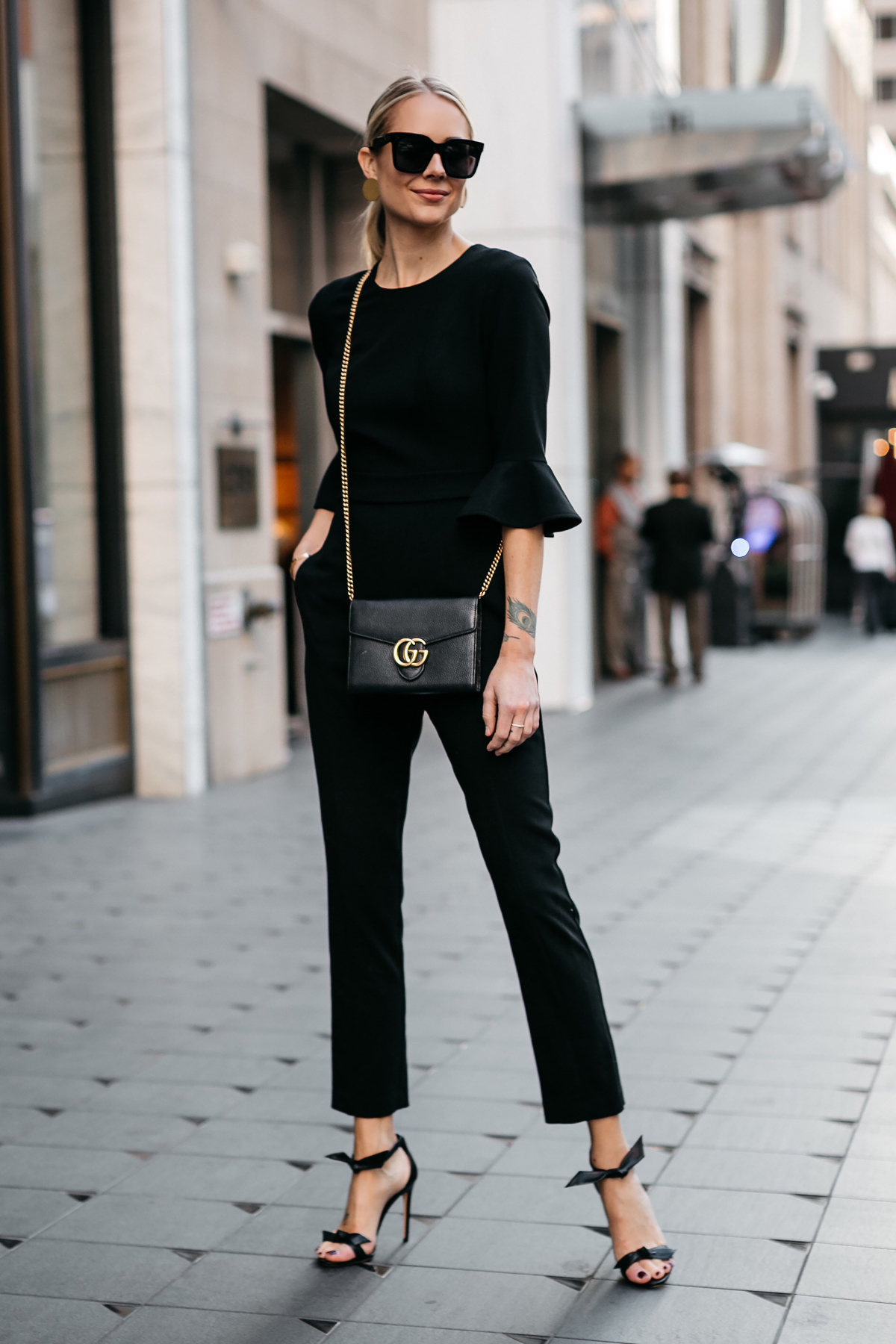 Blonde Woman Wearing Black Ruffle Sleeve Jumpsuit Gucci Marmont Black Handbag Black Bow Tie Heels Gold Disc Earrings Black Celine Sunglasses Fashion Jackson Dallas Blogger Fashion Blogger Street Style