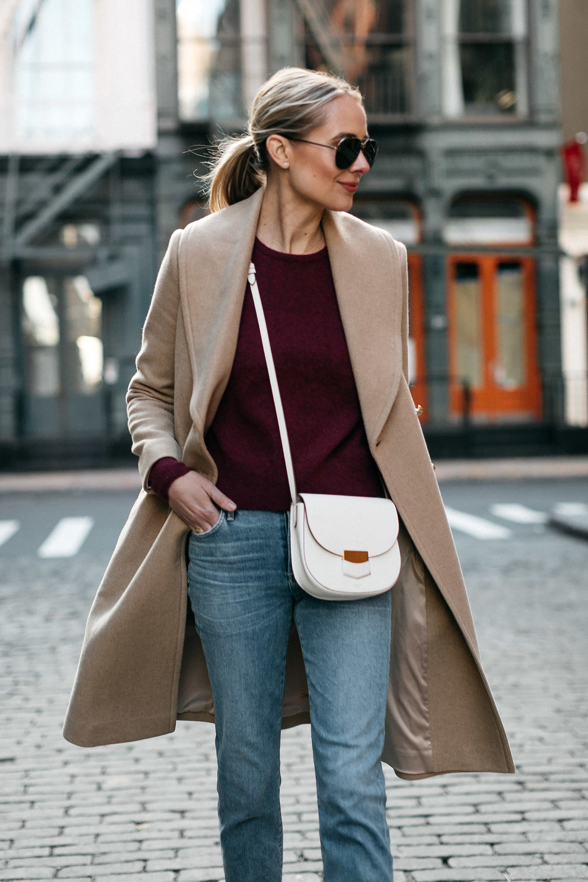 Blonde Woman Wearing Club Monaco Camel Coat Burgundy Sweater Denim Jeans Celine White Trotteur Handbag Fashion Jackson Dallas Blogger Fashion Blogger Street Style New York Fashion Week