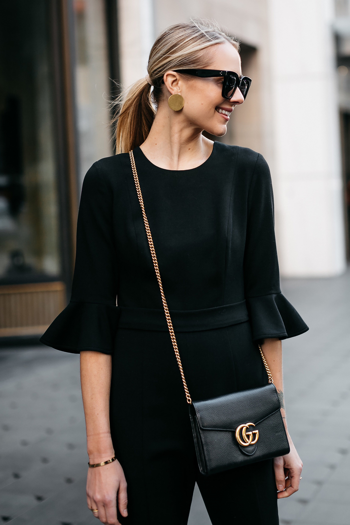 Blonde Woman Wearing Gucci Marmont Wallet Handbag Black Ruffle Sleeve Jumpsuit Gold Disc Earrings Black Celine Sunglasses Fashion Jackson Dallas Blogger Fashion Blogger Street Style