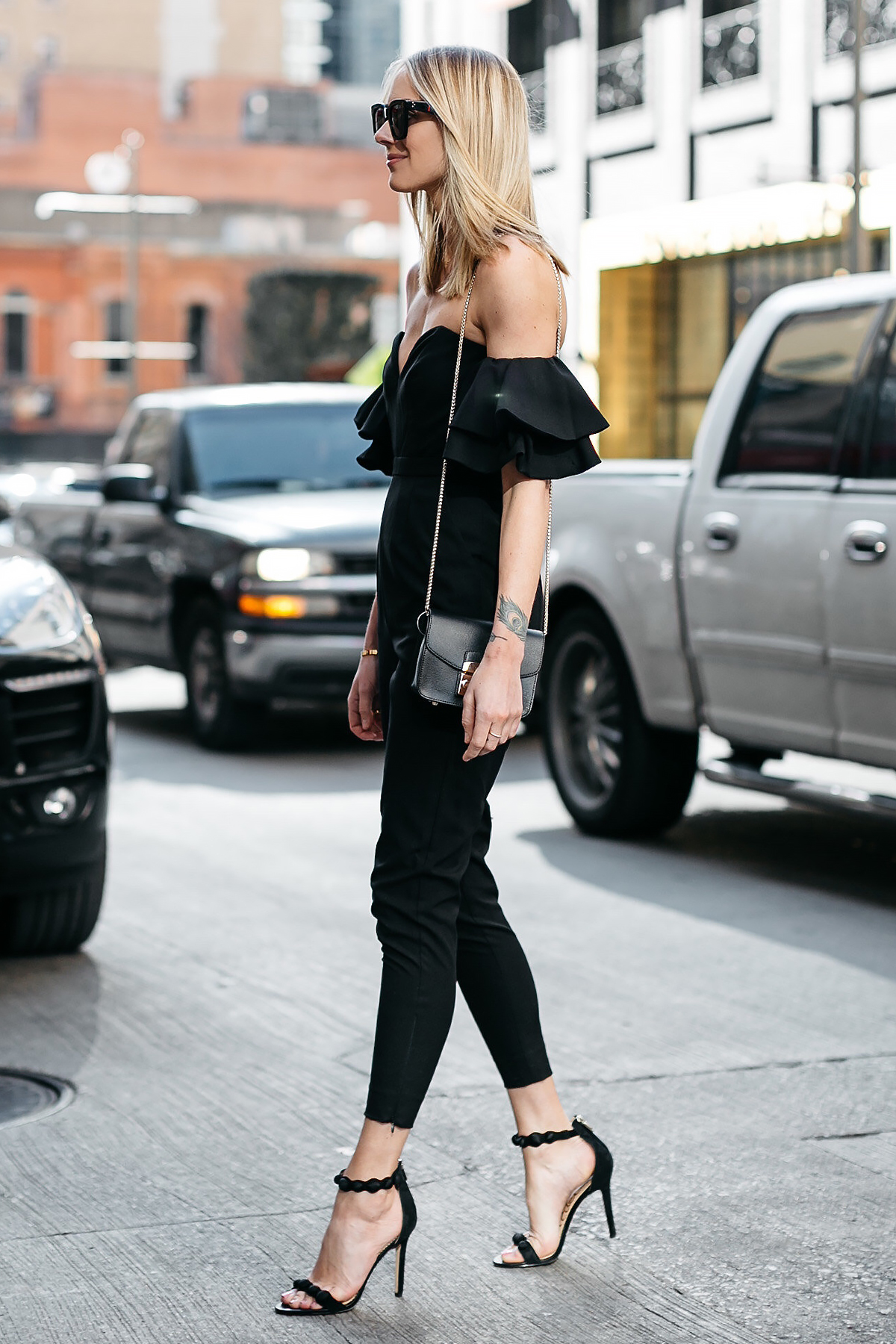 Blonde Woman Wearing Black off the Shoulder Jumpsuit Black Ankle Strap Heels Furla Black Handbag Fashion Jackson Dallas Blogger Fashion Blogger Street Style