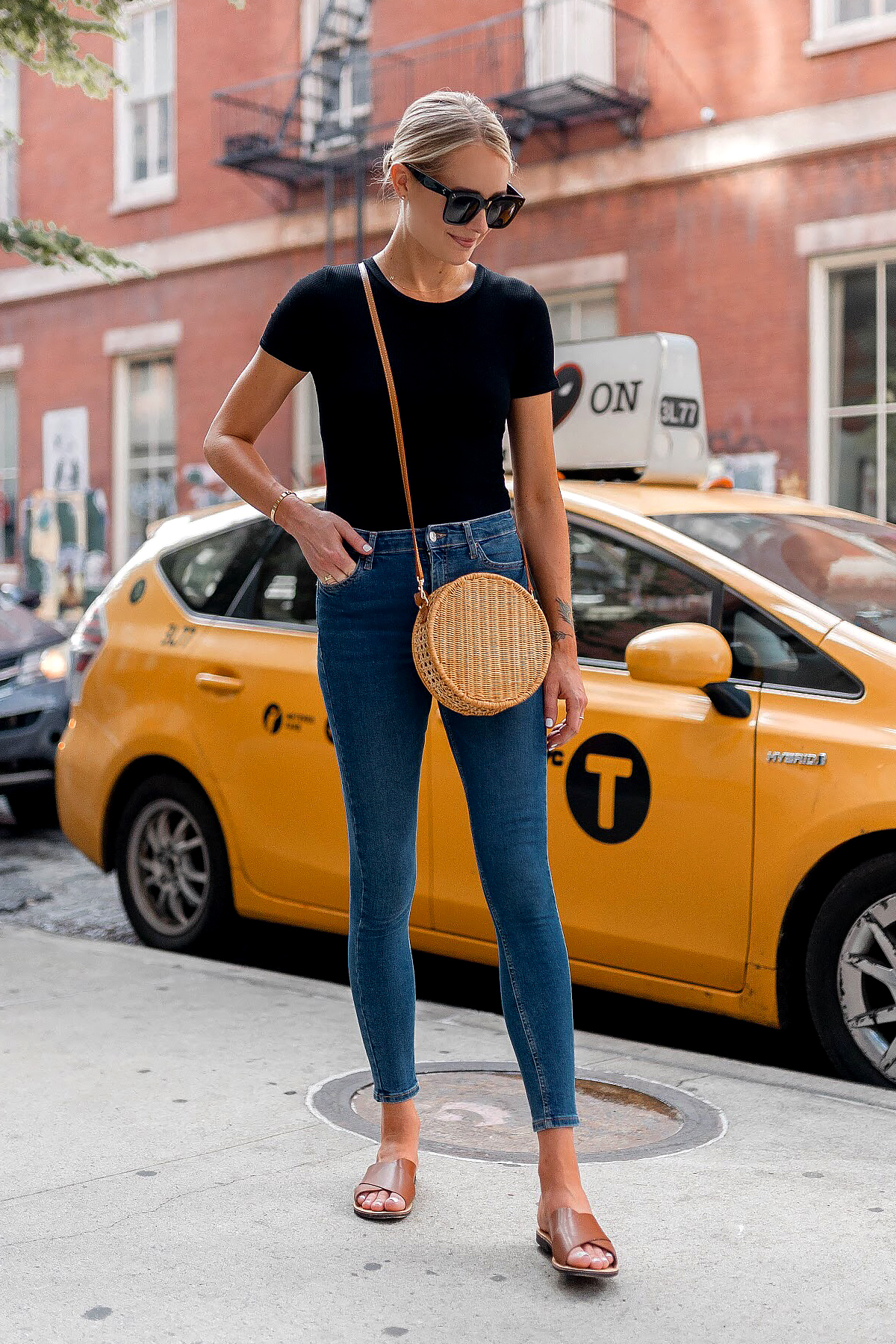 Blonde Woman Wearing Bloomingdales Black Short Sleeve Bodysuit Denim Skinny Jeans Tan Flat Sandals Circle Straw Handbag Black Sunglasses Fashion Jackson Dallas Blogger Fashion Blogger New York Street Style